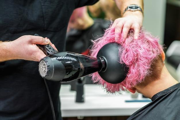 ブロードライヤーで短いピンクの髪を乾燥させる美容師の手のクローズアップ。