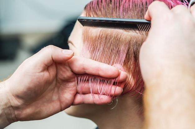 Парикмахер расчесывает волосы девушки во время стрижки.