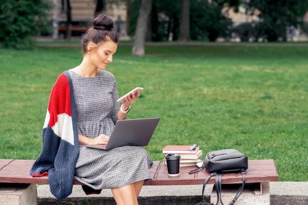 Студент взрослая девушка смотрит на смартфон в парке.