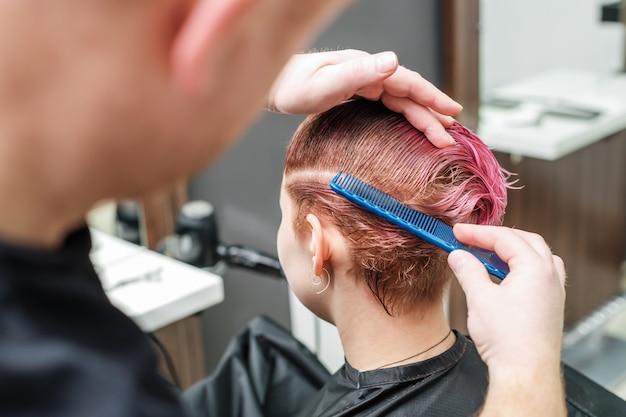 Парикмахер использует расческу для женских розовых волос в салоне красоты.