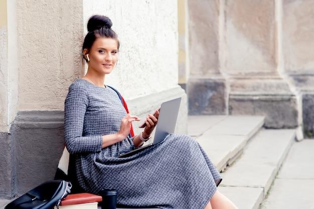 若い学生女性は大学の近くの階段に座っています。