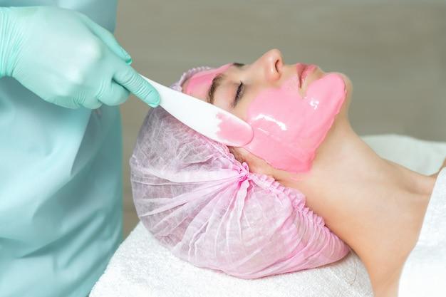 若い美しい女性がスパサロンでピンクの顔のマスクを受け取っています。