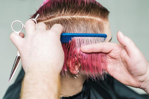 Парикмахер расчесывает розовые короткие волосы.