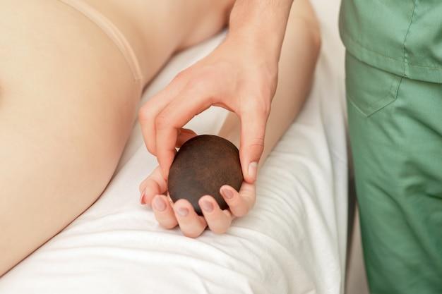 Мужской массажист кладет горячий камень на руку пациента.