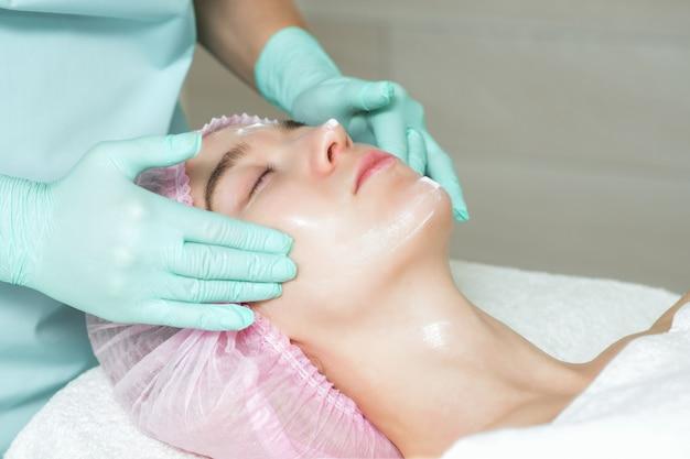 美容師は女性の顔にクリームを適用します。