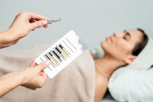 Косметолог берет ресницы пинцетом.