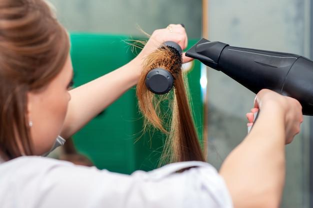 美容師は長い茶色の髪を乾燥させます。