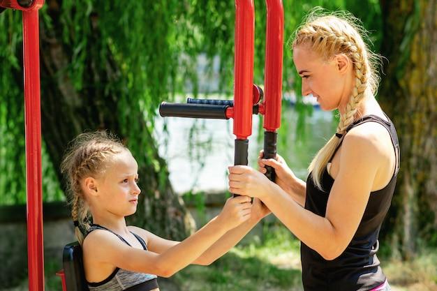 Женщина и маленькая девочка тренируются на тренажере.