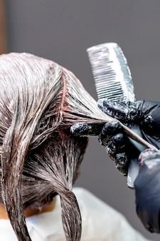Руки окрашивают волосы женщины.