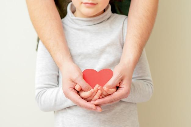 Бумага красное сердце в руках папы и ребенка.