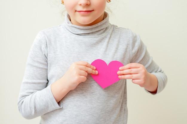 Маленькая девочка держит розовое сердце.