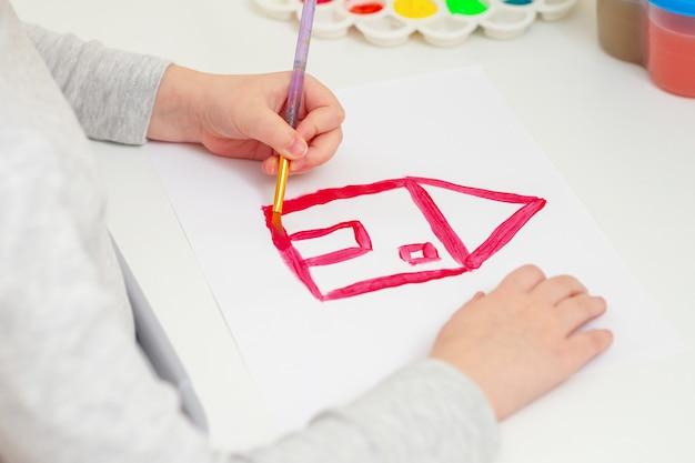 赤い家を描く少女の手。