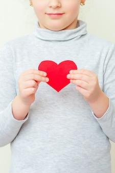 Маленькая девочка держит красное маленькое сердце.