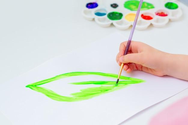 子供は緑の葉を描いています