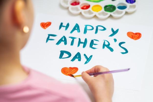 Ребенок рисует поздравительную открытку дня отца.