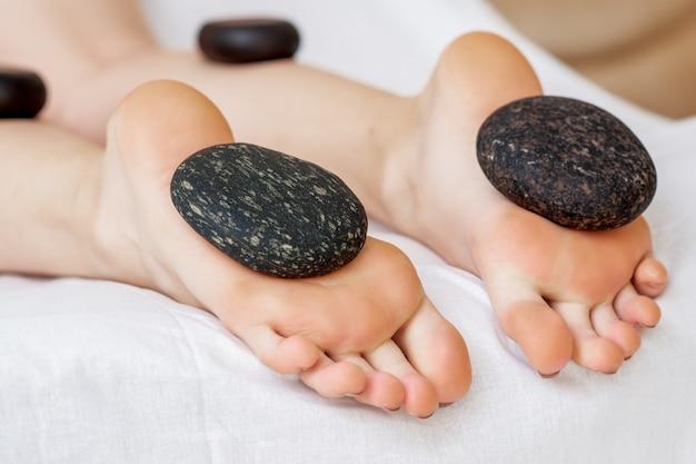 女性の足の上に横たわる熱い石