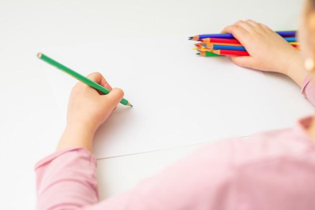 子供は色鉛筆で描いています。