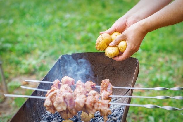 男はジャガイモとバーベキューの肉を準備します
