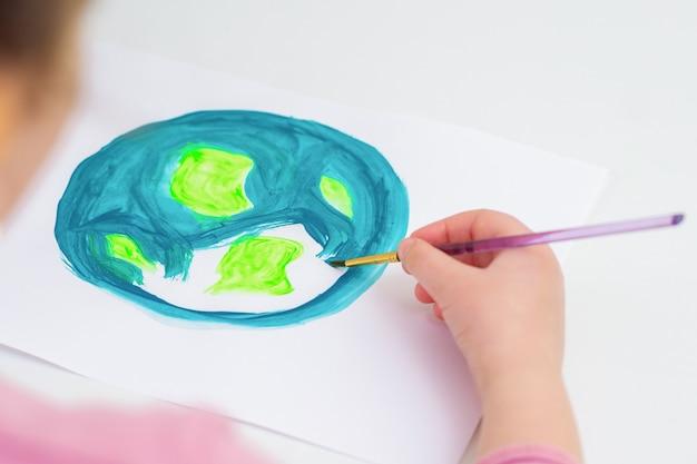 Маленькая девочка рисует землю.