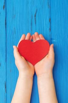 子供の手の中の赤いハート