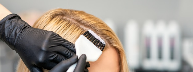 Парикмахер красит женские волосы клиента