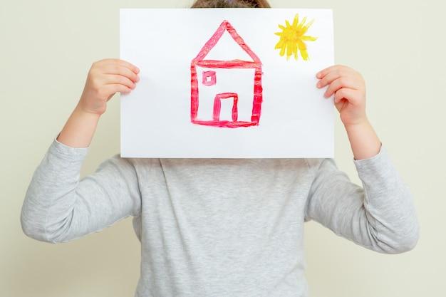 家の絵を抱いた子供