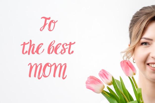 Молодая женщина с тюльпанами. поздравительная открытка с днем матери
