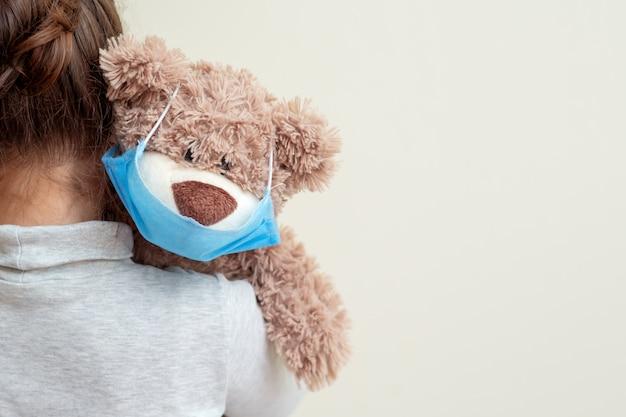 子供の肩に防護マスクをしたおもちゃのクマ