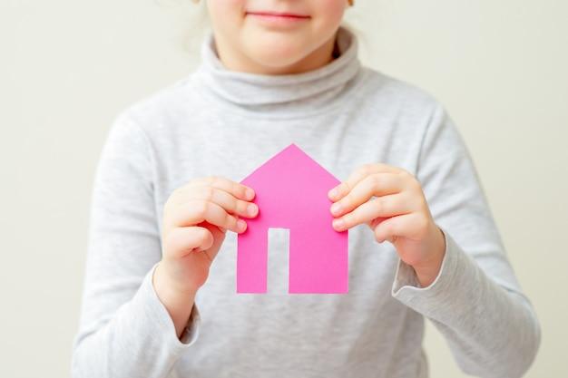 子供は紙のピンクの家を保持しています。