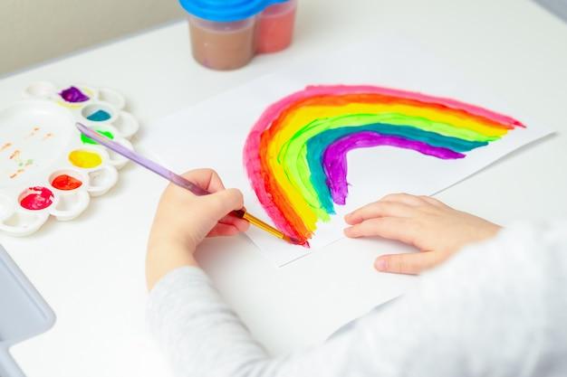 Крупным планом руки ребенка, рисование радуги