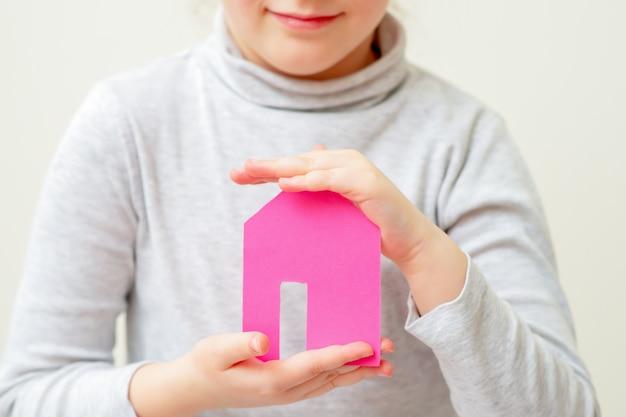 Ребенок держит бумажный розовый дом