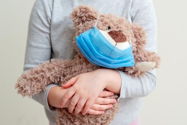 子供の手の防護マスクとおもちゃのクマ