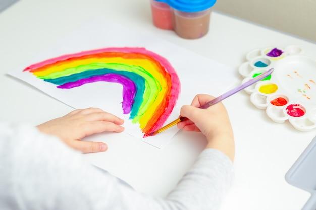 Ребенок рисует радугу