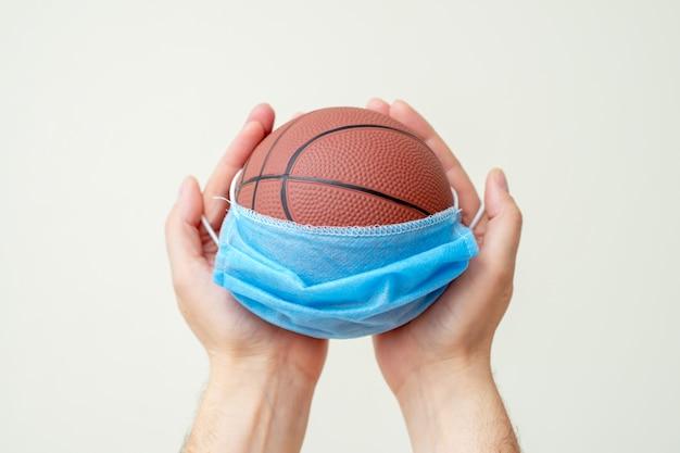 Баскетбольный мяч с медицинской маской в руках человека