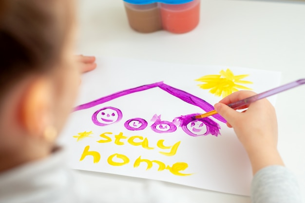 Ребенок рисует семью под крышей