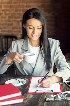 Женщина пишет в блокнот.