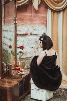 Ретро девушка сидит за туалетным столиком