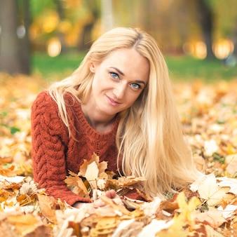 Женщина ложится на листья в осеннем парке