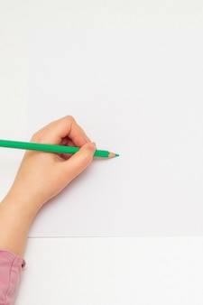 子供は白い空白の紙に描いています。