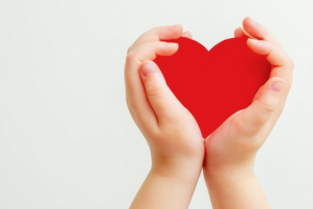 Бумажное красное сердце в руках ребенка