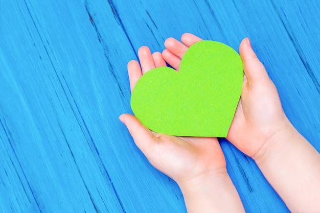 Зеленое сердце в руках ребенка