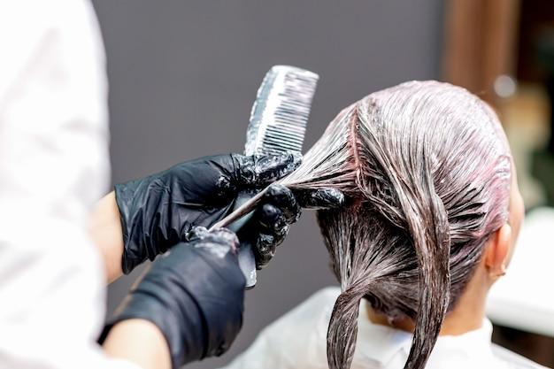 女性の髪を染める手