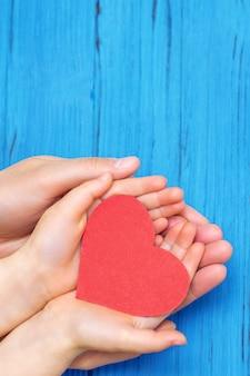 Руки ребенка и папы с красным сердцем