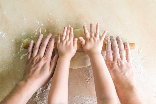 子供とお父さんの手は生地を転がし