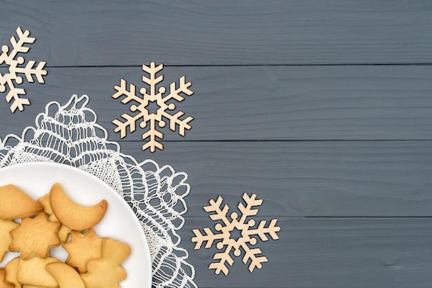 Тарелка с вкусным рождественским печеньем с декоративными снежинками на деревянном столе