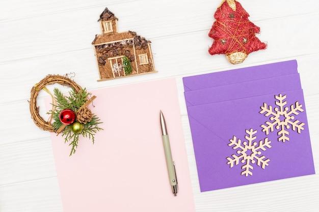 Чистый лист бумаги на белом деревянном столе с ручкой и конвертами