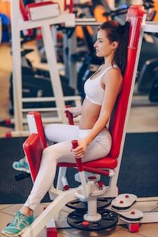 Молодая красивая спортивная женщина делает тренировки в тренажерном зале.