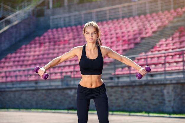 Красивая фитнес женщина с идеальным телом делает тренировки с ультрафиолетовыми гантелями на стадионе