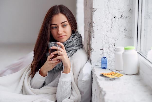 屋内で温暖化ドリンクを飲んで病気の不健康な女性