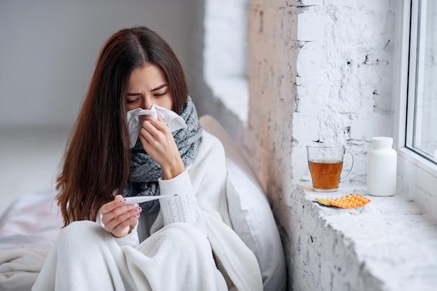 病気の女性は風邪をひいた、病気を感じ、紙拭きでくしゃみをする